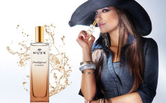 Portrait of beautiful young woman wearing hat, smelling perfume.