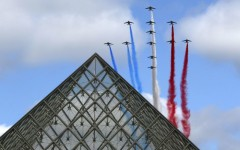Alphajets from the French Air Force Patrouille de France in the formation of a Croix de Lorraine cross and releasing trails of red, white and blue smoke, colors of French national flag, fly over the Pyramid of the Louvre Museum during the traditional Bastille day military parade in Paris, France, July 14, 2015.   REUTERS/Gonzalo Fuentes TPX IMAGES OF THE DAY